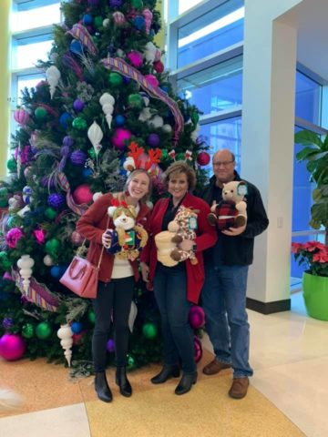 Western Sun members pose in front of christmas tree with donated toys for a donation drive