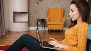 Young adult female sitting on floor against couch shopping online with laptop and debit card