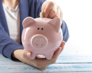 Female hands holding piggy bank and placing change inside