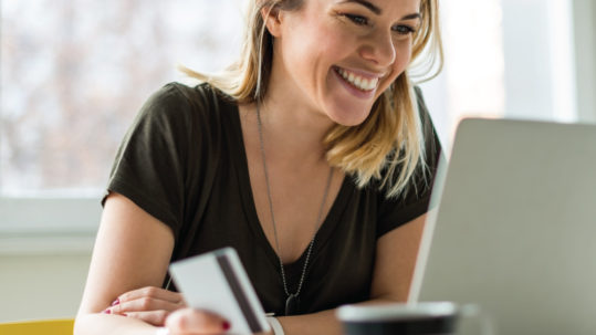 Young female shopping online using laptop holding debit card and smiling