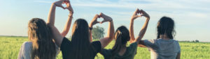group of young girls looking out at bright day and making hearts with their arms