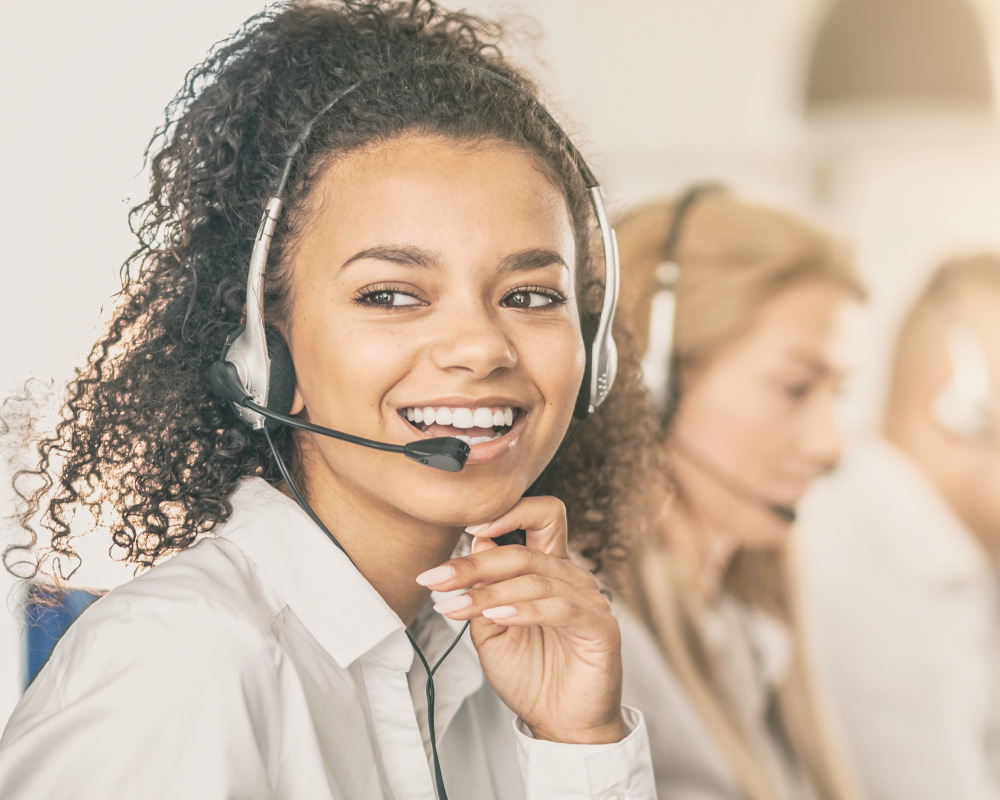 young female adult call center employee smiling as she answers a call on headset phone