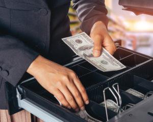 cash register open with business owner placing cash inside