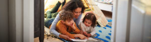 Mother with her two children, one boy one girl under her arms laying together on floor reading a book