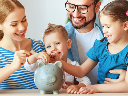 family all gathered around a piggy bank watching younger children place coins into piggy bank