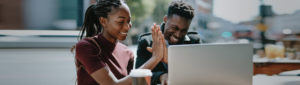 African American couple using laptop and high-fiving each other