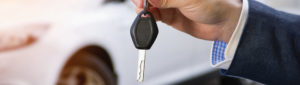 Car salesman holding key to car in front of car in background