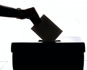 Person dropping a piece of paper into a voting ballot box.